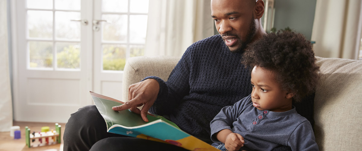 A father reads a book to his child